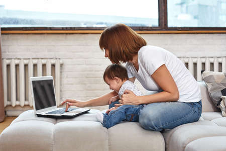 A woman with a child at a laptop sitting on a sofa. Work at home, freelancer, work during maternity leave for remote access.