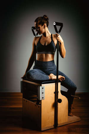 A young girl does Pilates exercises with a bed reformer, barrel machine tool. Beautiful slim fitness trainer on a background of a reformer gray, low key, light art. Fitness concept, healthy lifestyle.