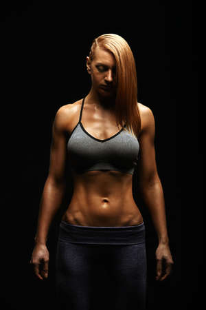 Young fit women in sports equipment, sports embossed female body, black background, hard light. Copy space, sports banner