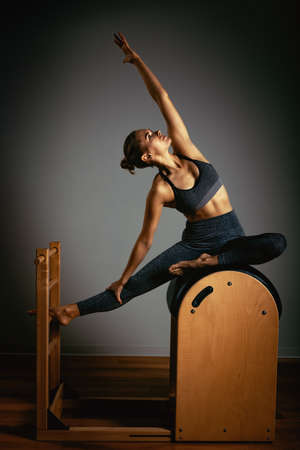A young girl does Pilates exercises with a bed reformer, barrel machine tool. Beautiful slim fitness trainer on a background of a reformer gray, low key, light art. Fitness concept, healthy lifestyle Foto de archivo