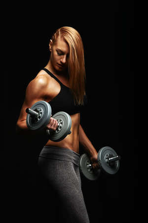Young fit woman in sports equipment with dumbbells in her hands, sports embossed female body, black background, hard light. Copy space, sports banner 스톡 콘텐츠