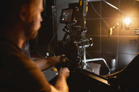 Video production backstage. Behind the scenes of creating video content, a professional team of cameramen with a director filming commercial ads. Video content creation, video creation industry