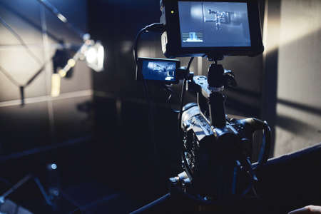 Video production backstage. Behind the scenes of creating video content, a professional team of cameramen with a director filming commercial ads. Video content creation, video creation industry, Low k