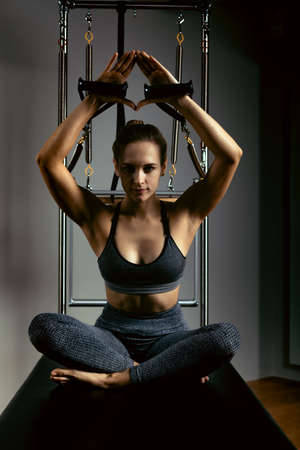A young girl does Pilates exercises with a bed reformer, barrel machine tool. Portrait shot of a beautiful slim fitness trainer on a reformer gray, low key, light art background. Fitness concept, heal