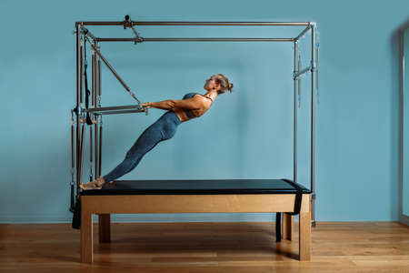 A young girl does Pilates exercises with a bed reformer, barrel machine tool. Beautiful slim fitness trainer on the background of a reformer doing various exercises gray, low key, light art. Fitness c