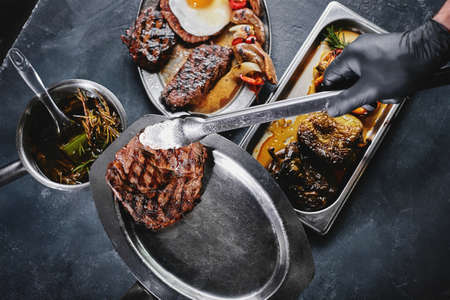 Grilled meat platter. Assorted delicious grilled meat with vegetables. Grilled mixed meat with pepper sauce and vegetables. Chef's hands spread meat on a plate.