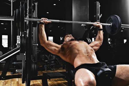 Young muscular man lifting a barbell bench press in the gym. Sport, movement, life. The concept of a healthy lifestyle, regular training, development of the pectoral muscles.