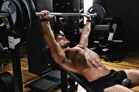 Gut aussehender junger Mann beim Bankdrücken im Fitnessstudio, Fitnessmotivation, Sportlebensstil, Gesundheit, athletischer Körper, Körper positiv. Filmkorn, selektiver Fokus