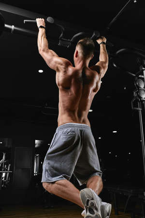 Strong man doing pull-ups on a bar in a gym. Imagens