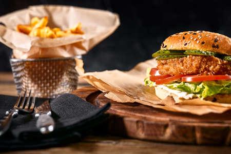 Juicy burger on the board, black background. Dark background, fast food. Traditional american food. Copy space. Zdjęcie Seryjne