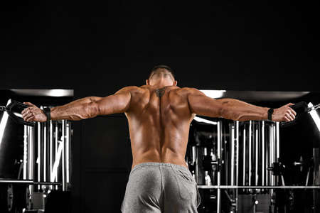 Rear view of a tense bodybuilder in the gym in a dark atmosphere. A muscular man with a beautiful body doing an exercise. Sport concept. Fitness motivation, forward movement, copy space, sports banner.