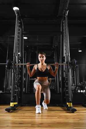 Attractive shape young sporty focused fitness girl with ponytail doing biceps exercises while sitting on the bench and raising dumbell in the gym at night.