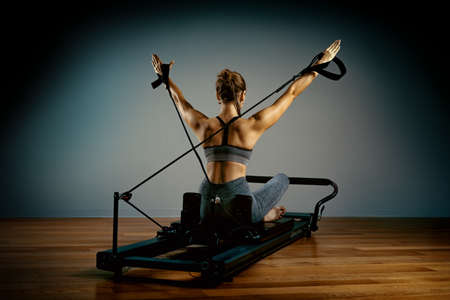 Young girl doing pilates exercises with a reformer bed. Beautiful slim fitness trainer on reformer gray background, low key, art light. Fitness concept. Stock Photo