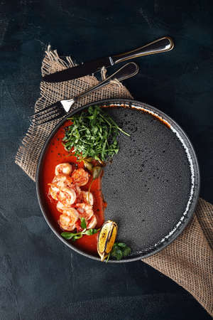 Grilled king tiger prawns with tomato sauce and arugula, beautiful serve from the chef, gray plate gray background. Bright beautiful flow of seafood, copies of space food photo.