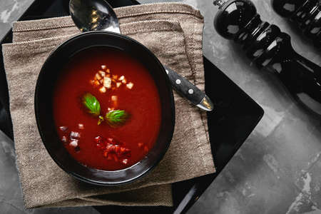 Tomato soup in a black bowl on a gray stone background. View from above. Copy space. Gray background. calm light. Food concept
