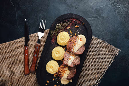 Grilled pork chops with mashed potatoes. On a dark wooden background, rustic style. Food photo
