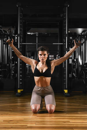 Beautiful athletic young Caucasian girl working out in gym training chest. pumping up pectoral muscles with dumbbells and on crossovers gaining. weight and poses fitness and bodybuilding concept