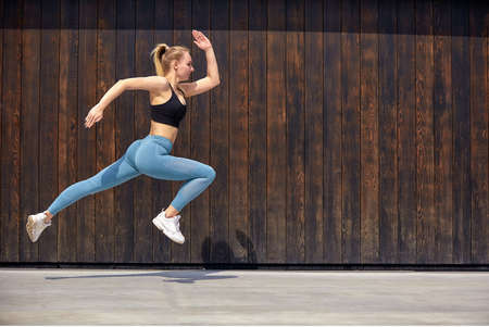 Young sporty beautiful woman with the right body, jumping and running, hurry on a wooden wall background. Gymnast jumping high with a toothy smile, full length, on the street