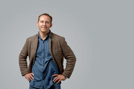 smiling old casual man in leather jacket with hands in pockets standing against gray studio wall