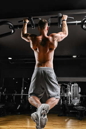 The athlete does a pull-up on the horizontal bar. A man in great shape is doing pull-ups on the horizontal bar from the entrance hall. Dark background, sport motivation.