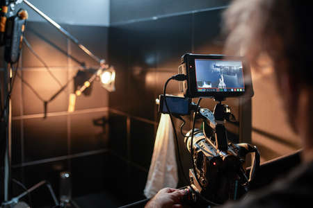 Behind the scenes of filming movies and video products, setting up equipment for shooting video and sound. The concept of producing video content for social networks, TV and blogs. Archivio Fotografico
