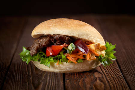 close up of kebab sandwich on wooden background.