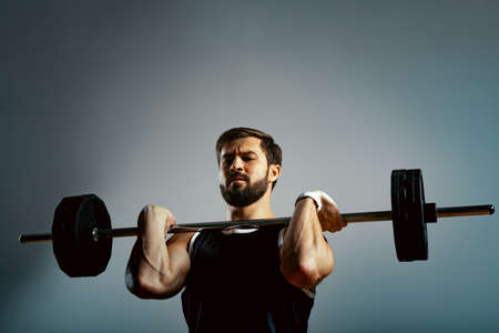A man does exercises with a barbell on a gray background. Fitness concept, sports motivation. Standard-Bild