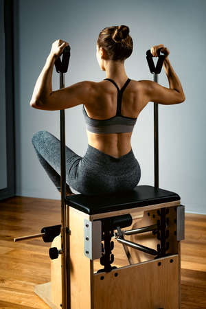 Young girl exercises on a bed of Pilates reformers, in the hall on a background of a gray wall. Fitness stretching concept. Healthy body, yoga, Pilates, copy space.