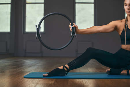 The girl is training her hands with a fitness expander in the gym, doing push-ups, training the upper body, shoulders, chest, triceps. Fitness motivation, copy space.