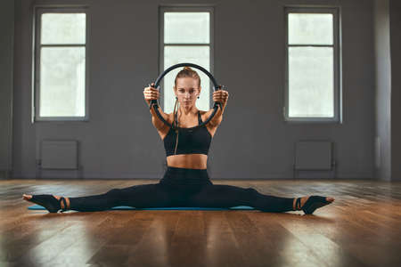 Fitness trainer with a beautiful figure poses for the camera during a workout in the gym with an ispander ring. Fitness motivation. All or Nothing, Healthy Living