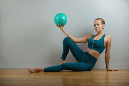 The young, beautiful, sports girl doing exercises on a fitball at the gym on gray background Stock Photo