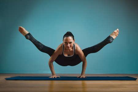 Sporty young woman doing stretching. Slim girl practicing yoga indoors on blue background. Calm, relax, healthy lifestyle concept.
