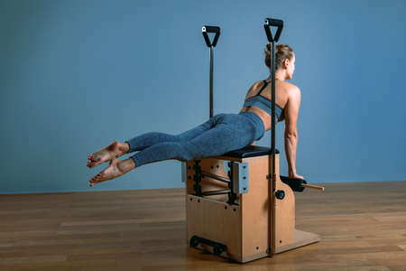 Pilates woman in a reformer doing stretching exercises in the gym. Fitness concept, special fitness equipment, healthy lifestyle, plastic. Copy space, sport banner for advertising Stock Photo