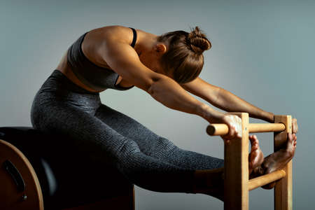 Pilates reformer bed, close-up, woman and instructor doing exercise on reformer simulator for treatment of musculoskeletal system