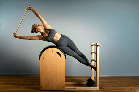 Pilates trainer exercises on a pilates barrel. Body training, perfect body shape and posture correction opporno motor apparatus. Copy space.