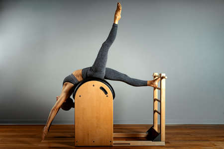 Pilates, fitness, sport, training and people concept - woman doing exercises on a small barrel. Correction of impellent apparatus, correct posture.