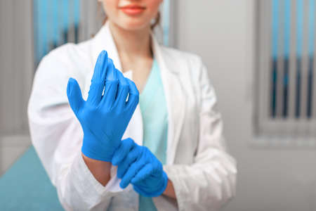 Doctors hands putting on latex gloves in a hospital. Woman in a doctors smock in latex gloves. Protection against virus and bacteria. Kovid 19. Health