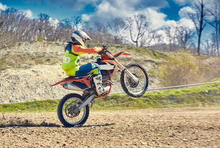 Motocross, a rider stands on the rear wheel of a bike, Riding on the rear wheel. Extreme, industrial, motorcycle cross-country riding for extreme
