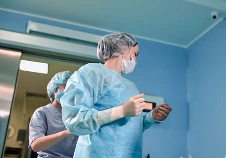 A team of surgeons is preparing for surgery. Surgeons wear sterile clothing before surgery with the help of nurses, sterile gowns, gloves, masks, in the intensive care unit
