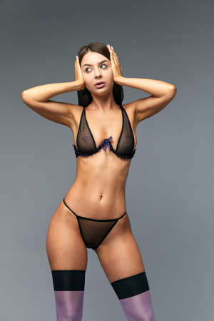 The body of a young and beautiful woman in female underwear showing lingerie to the camera, isolated on a gray background. Fashion concept, copy space. Standard-Bild