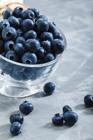 Blueberries on a black background, close-up, fresh berry in a bowl on a concrete background with a wrapped envelope with a berry. copies of space, delivery of berries.