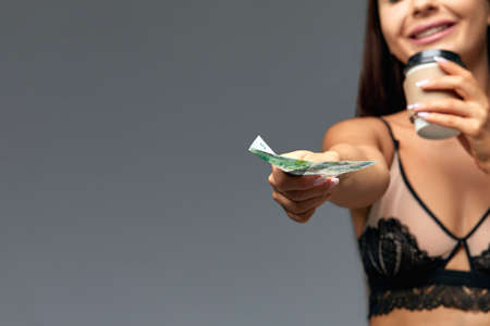 Beautiful Italian woman with coffee in her underwear giving money for coffee, on a gray background with copy space. Advertising banner, good and energetic morning. Girl and coffee concept - great mood in the morning.