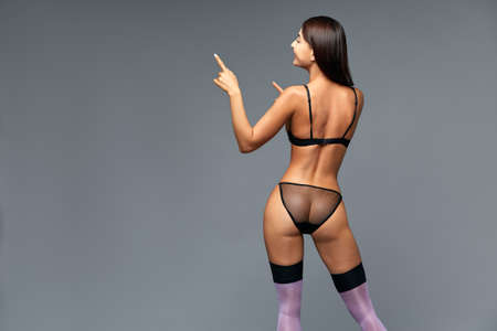 Lingerie, stockings, panties. A girl in beautiful lace lingerie is having copy space. Gray background, copy space. Banque d'images