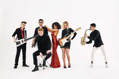 Entertaining concept, teamwork. International group of musicians on a white background, guitarist, drummer, soloists, saxophonist.
