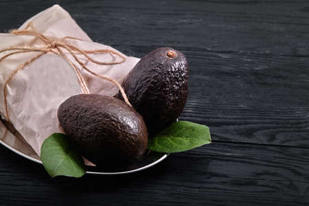 Dark avocado haas, on a dark wooden background, eco packaging, food delivery, copy space.