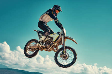 racer on mountain bike participates in motocross race, takes off and jumps on springboard, against the blue sky. Close-up. concept of extreme rest, sports racing. 写真素材