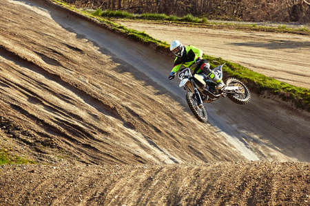 Motocross driver in action accelerating the motorbike takes off and jumps on springboard on the race track Banque d'images