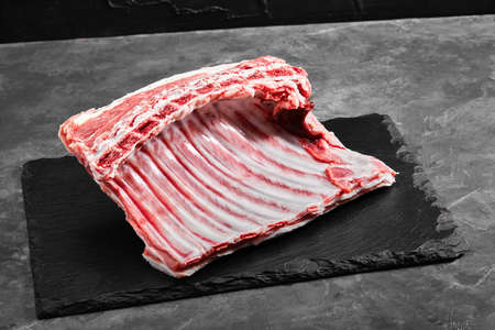 Lamb ribs fresh meat, with eco-friendly packaging. Food Delivery Concept. copy space, dark background Фото со стока