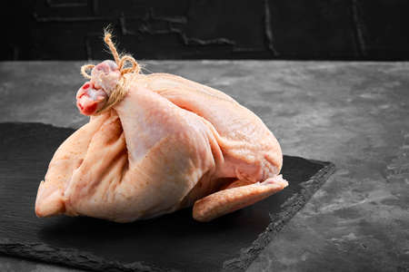 Fresh chicken carcass on a gray background, fresh meat, copy space, photo for grocery stores. dark background