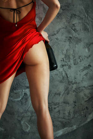 Woman wearing short red dress showing her long, workout sexy legs and hips. Holding a bottle of champagne. Rear view